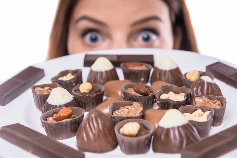 a woman holds a plate of small chocolates