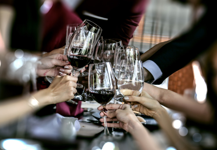 group clinking glasses of wine at dinner event