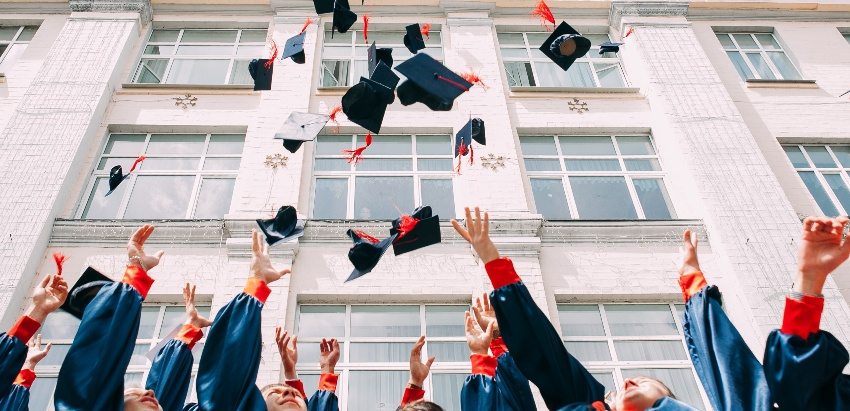 college graduates tossing their graduation caps