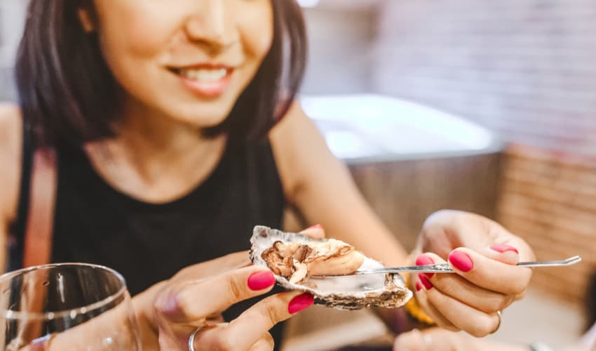 woman eating oysters from the shell
