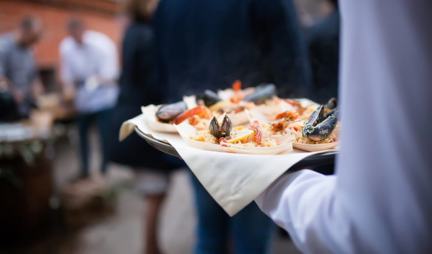 seafood paella being carried by a waiter