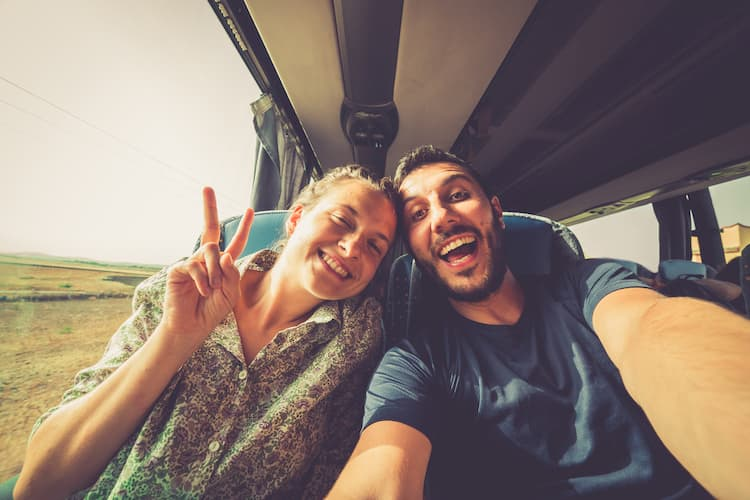 Young man and woman taking a selfie together on a charter bus trip.
