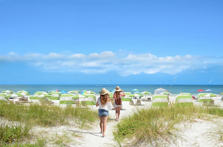 Girls walking on the beach on summer vacation. Beach chairs and parasols on beautiful white sand in the background.