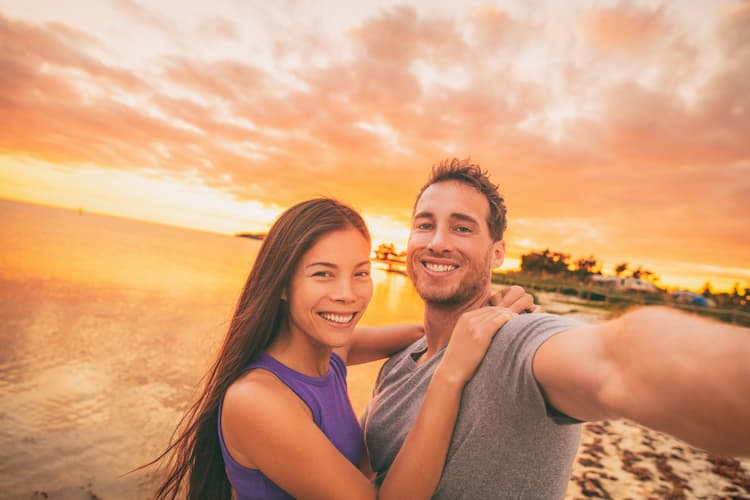 Happy selfie couple tourists on USA travel taking photo at sunset on Florida beach.