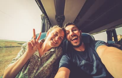 Two people enjoying a road trip on a charter bus