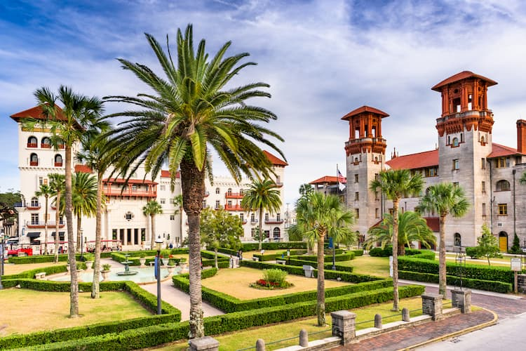 Town square of St. Augustine Florida filled with palm trees, a garden, and Spanish architecture