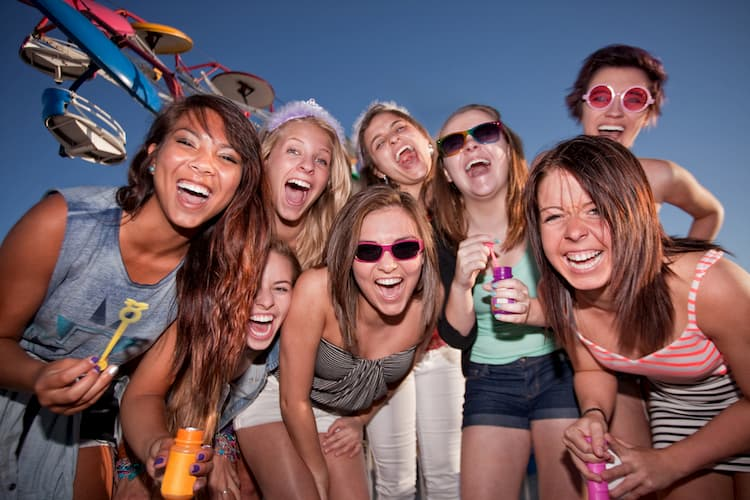 Group of happy women blowing bubbles and laughing at an amusement park.