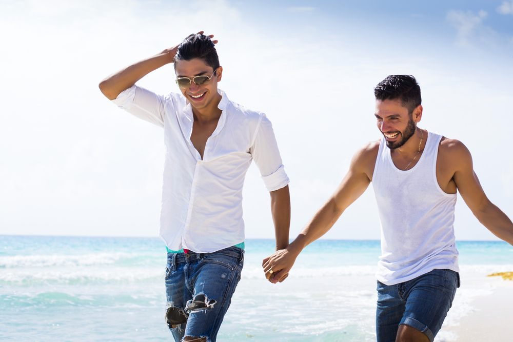 Two men holding hands on the beach