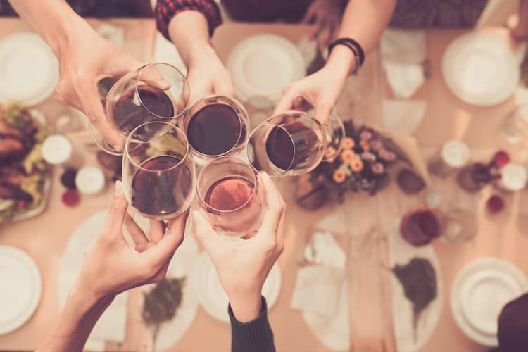 friends toast their wine glasses over an upscale table setting