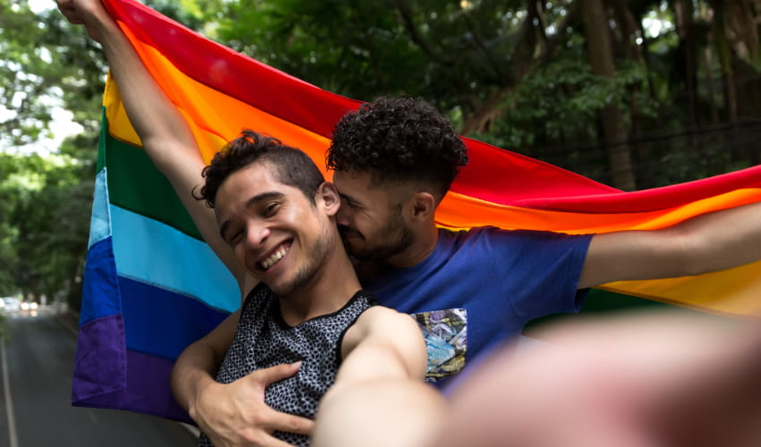 two men embrace and hold up a rainbow flag at a Pride parade