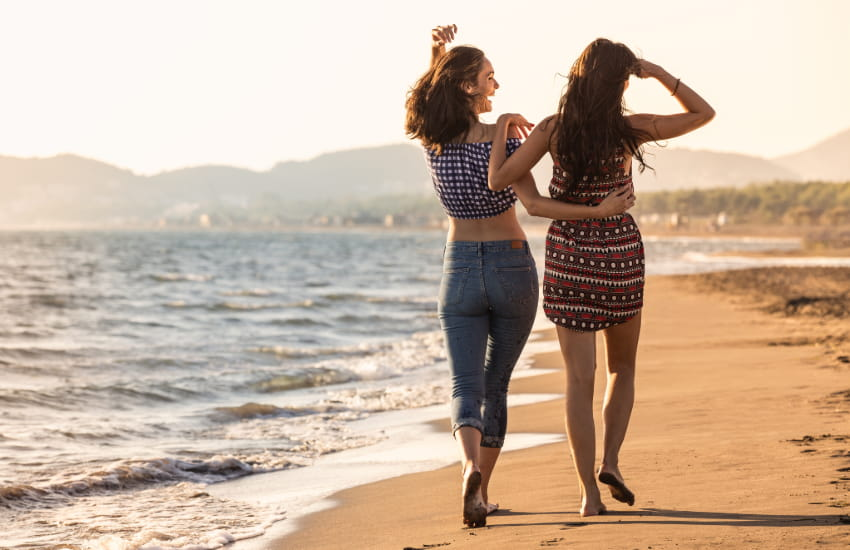 two women walk on a beach with their arms around each other