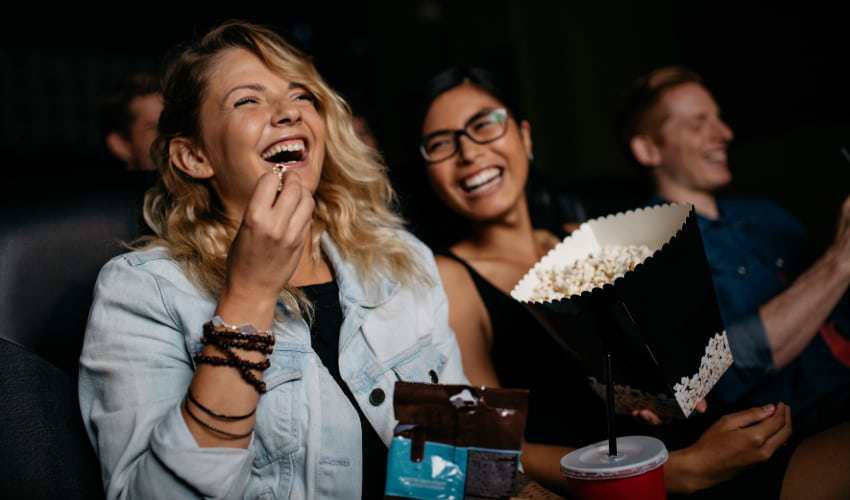 two women laugh and eat popcorn as they watch a film in a movie theater