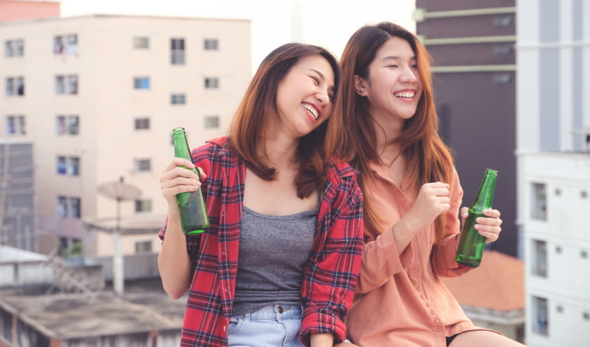 two women laugh and drink beers in a relaxed bar setting