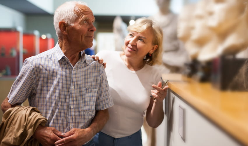 an older woman and man explore a museum and talk