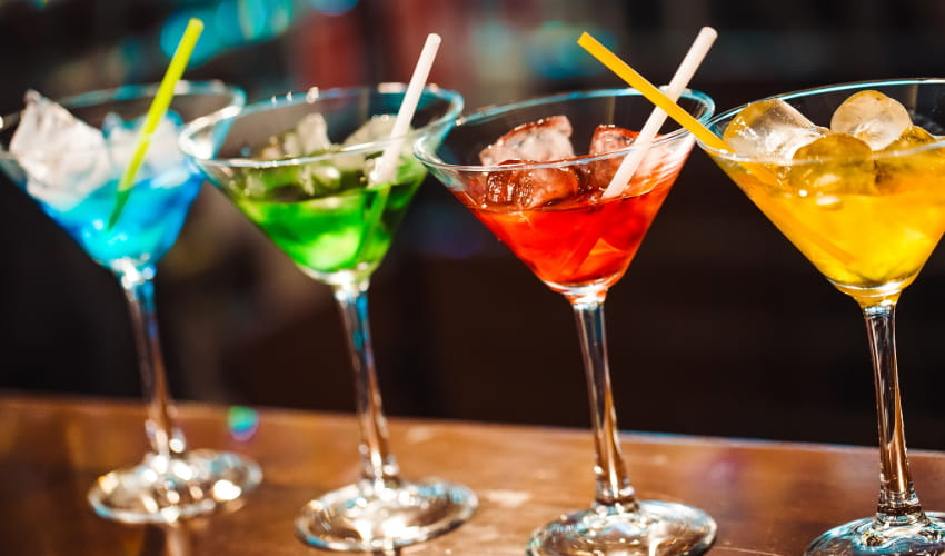 a lineup of rainbow-colored cocktails on a bartop