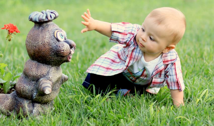 a baby plays with a caterpillar figurine on a lawn