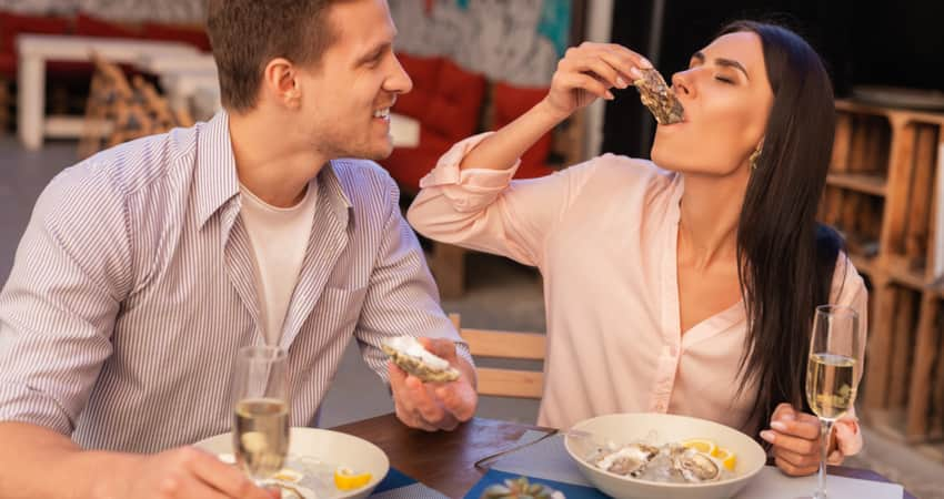 A man and woman having raw oysters and white wine