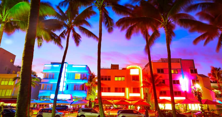 The Art Deco Historic District at sunset, neon signs of a vairety of colors illuminating the palm trees on the beach
