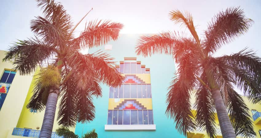 The exterior of a blue and yellow Art Deco building with palm trees