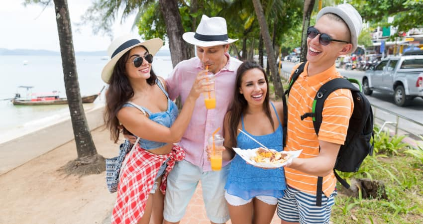 A group of tourists walk on a beach sidewalk, eating street food and drinking fresh juice