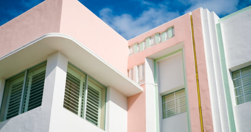 The exterior of an Art-Deco-era hotel painted white, pastel pink, and mint green