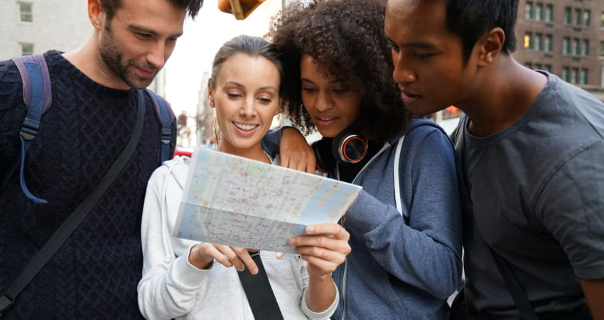 A group of tourists check a map in a city sidewalk