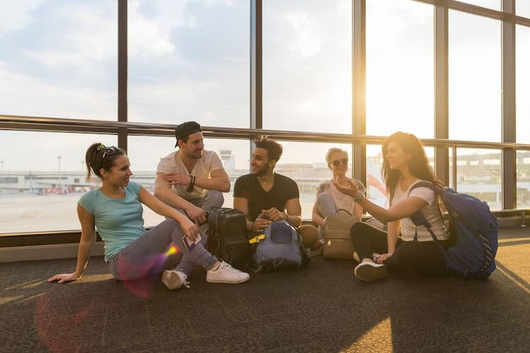 Five friends sitting on floor of airport