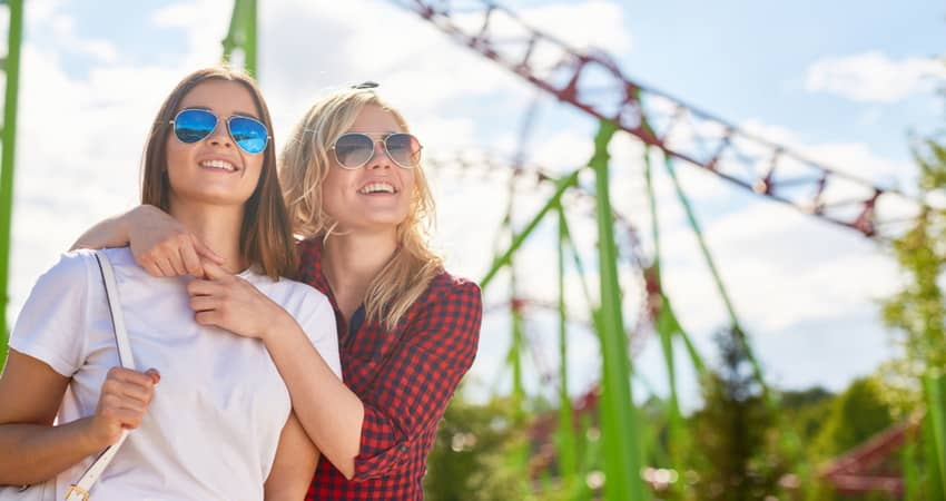 two women affectionately holding eachother at a theme park