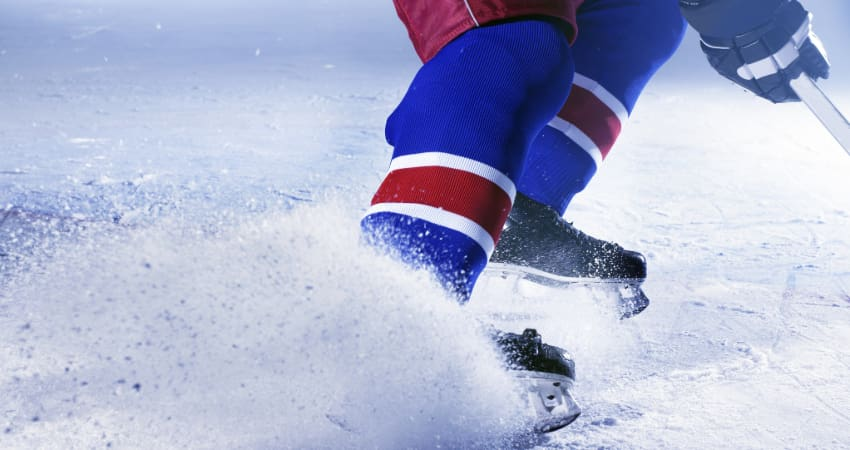 Closeup image of a hockey player turning sharply on an ice rink, kicking up shreds of ice
