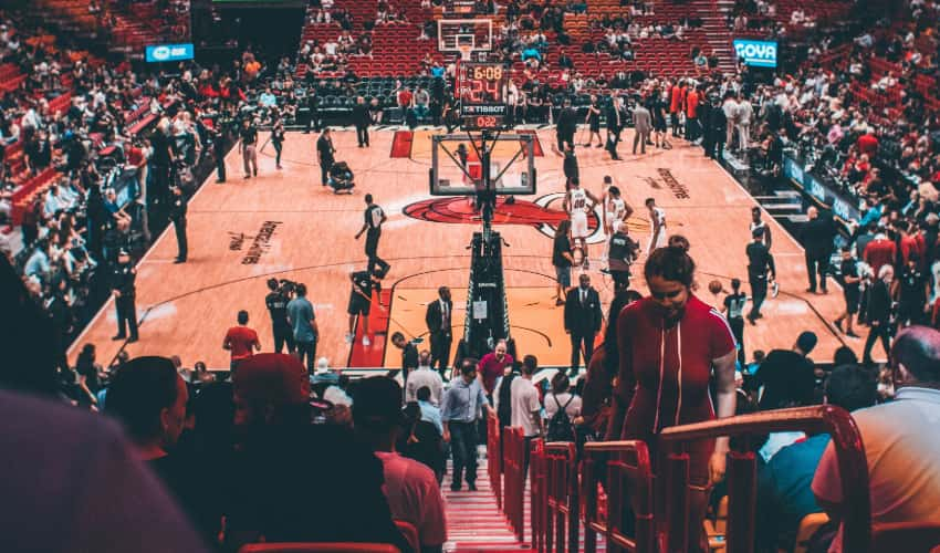 Fans, coaches, and players walk around a basketball court before a game, the Miami Heat logo visible in the middle of the court