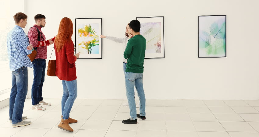 A group of art viewers tour a crisp white  museum