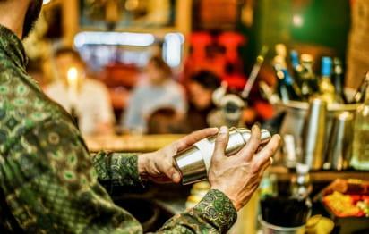 a bartender mixes a drink with a mixer