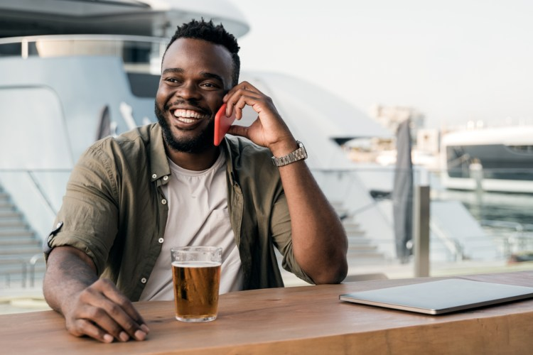 a man calls friends on his phone while he waits at a brewery