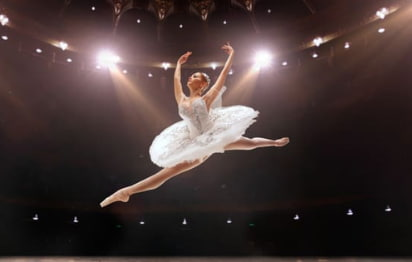 a ballerina floats mid-air with her arms up and her legs split