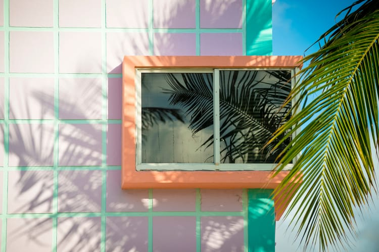 a corner window with an orange trim against a pink tile building with palm leaves in the foreground