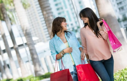 two friends smile at each other while they carry shopping bags and walk down a miami street