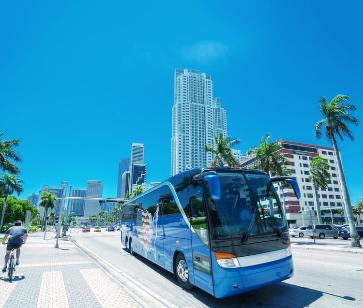 a blue charter bus parked on the side of a miami street