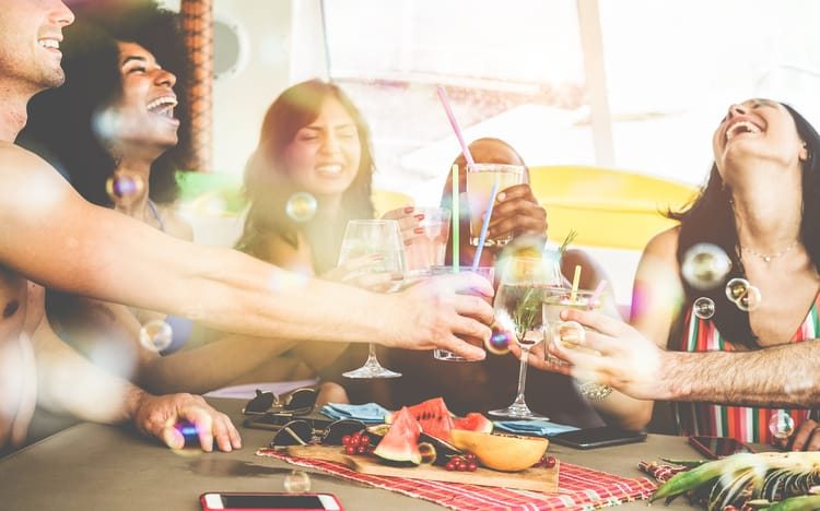 friends cheers their glasses and smile around a table filled with food