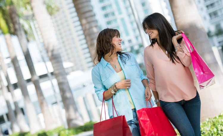 friends smile at each other while they hold shopping bags and walk through miami
