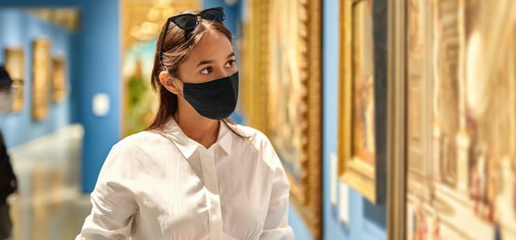 a woman wearing a mask looks at a painting in an art museum