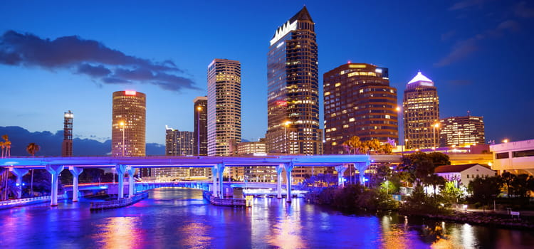 the tampa skyline after dark, with the city lights illuminating the river