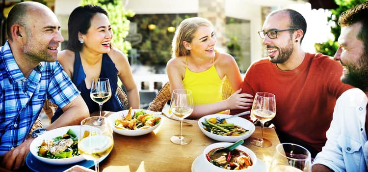 friends gather around a table outside to eat and drink