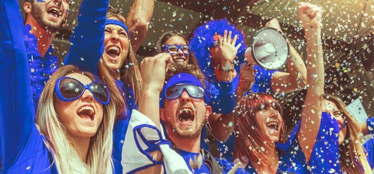 sports fans wearing blue celebrate and cheer while blue confetti falls
