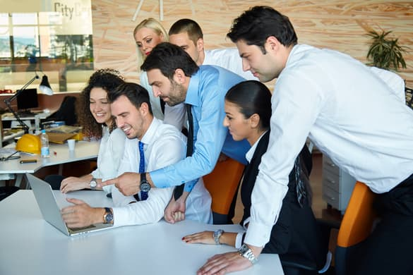 business people huddled around a desk working together