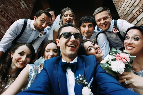 bride and groom taking a fun photo with wedding party