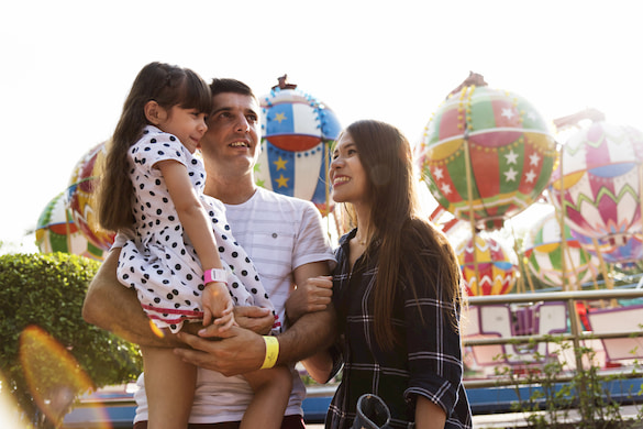 a family smiles while they enjoy a carnival in florida