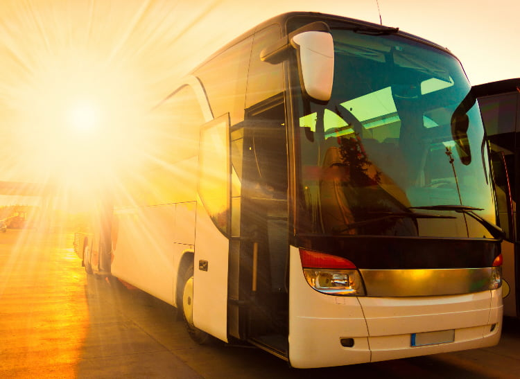 A charter bus parks with the setting sun behind it