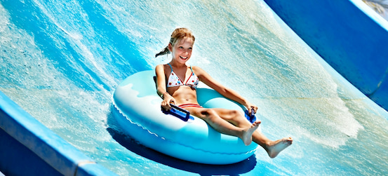 a child in an inner tube rides a water slide at Adventure Park in Tampa
